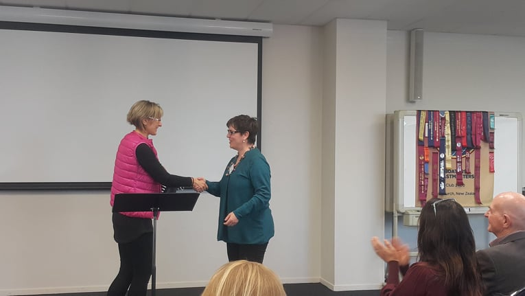 Two women in front of an audience, shaking hands