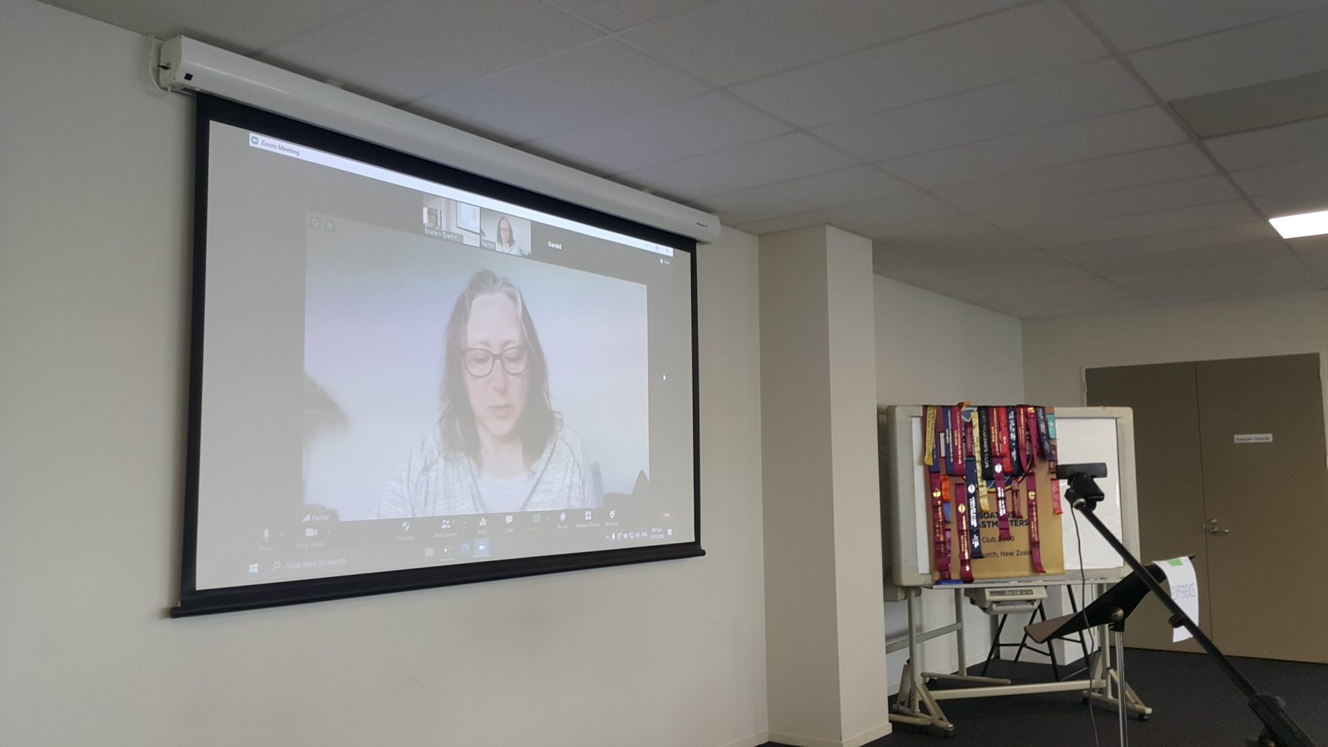 Woman projected speaking via Zoom on a screen