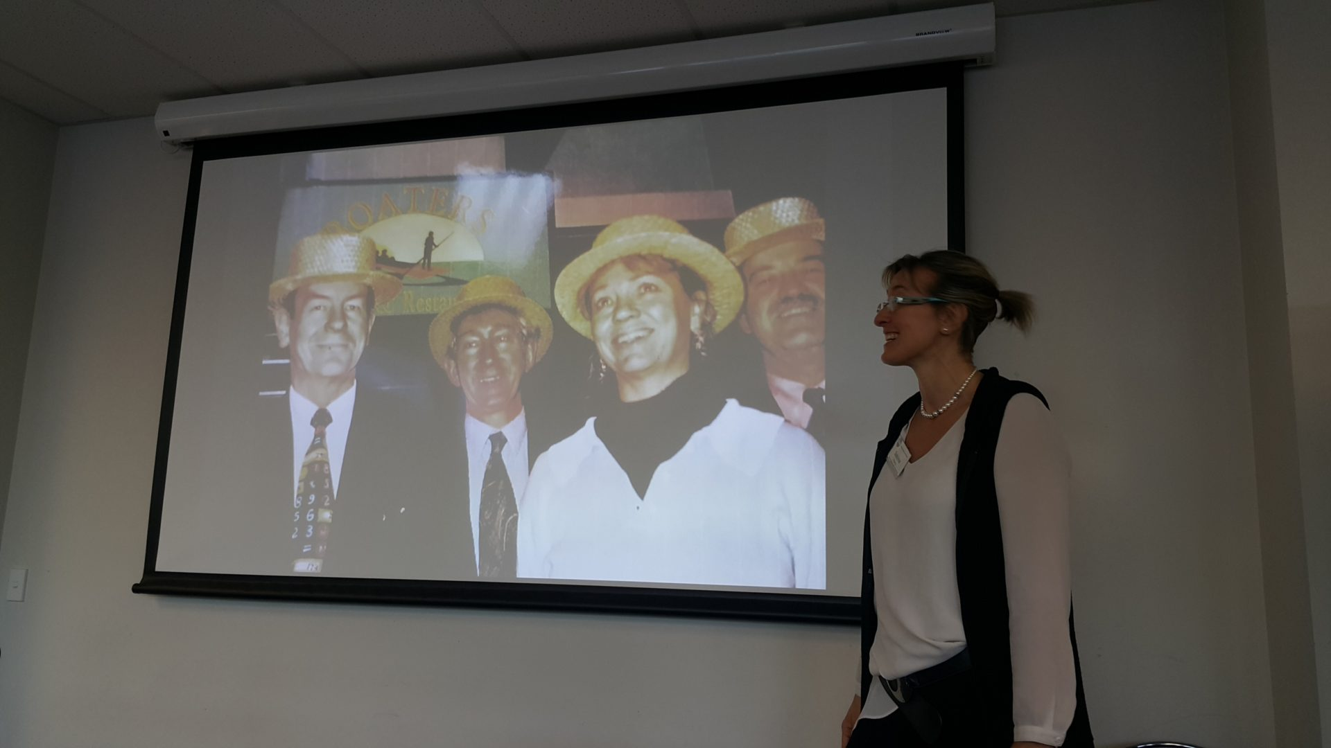 woman presenting a slide showing a group of four people