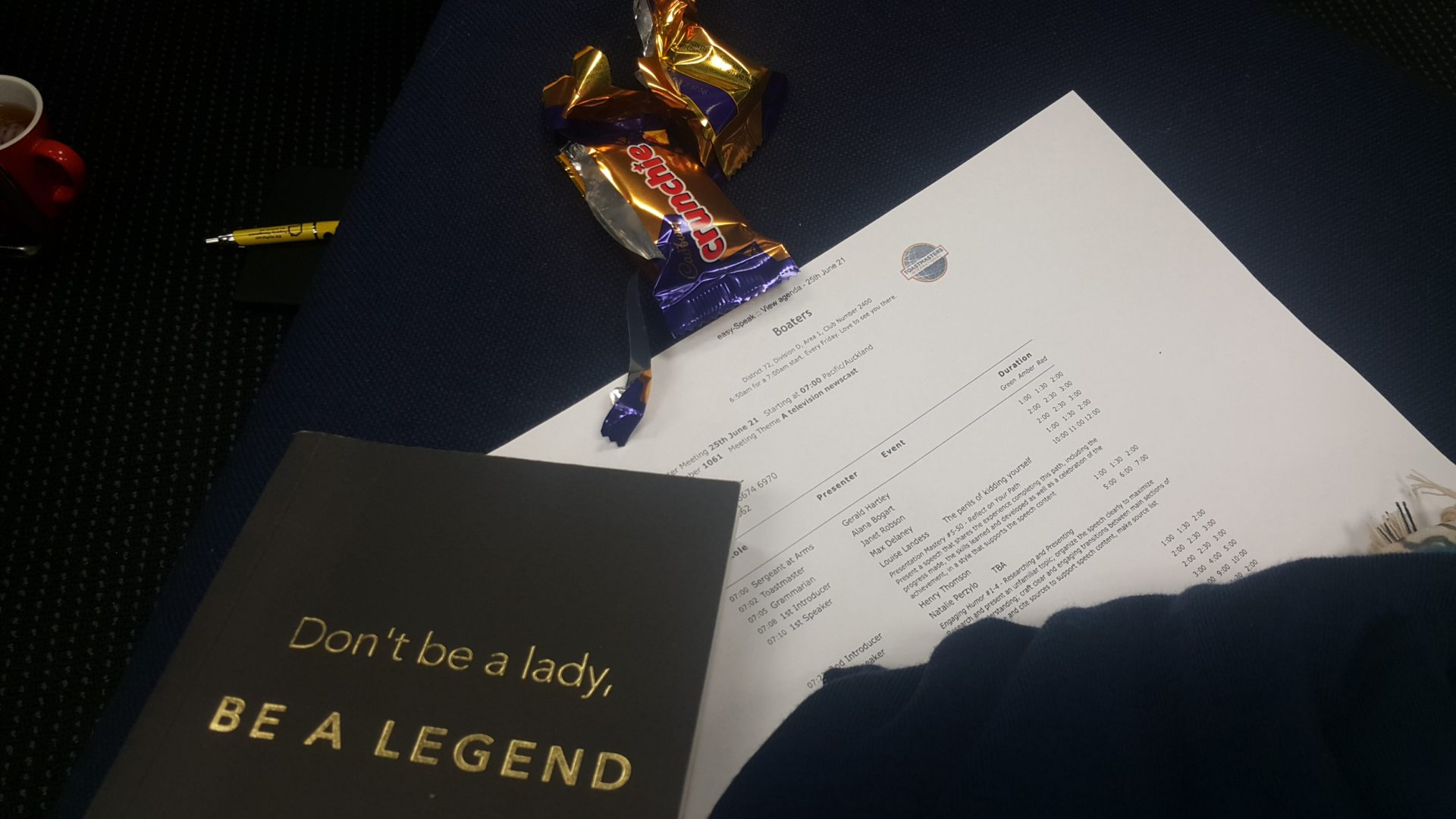 Notebook, printed agenda and chocolate bar wrapper on a chair