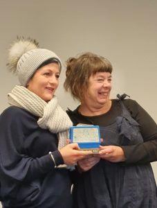 Two women posing with a trophy. One wearing an outstanding white bobble hat