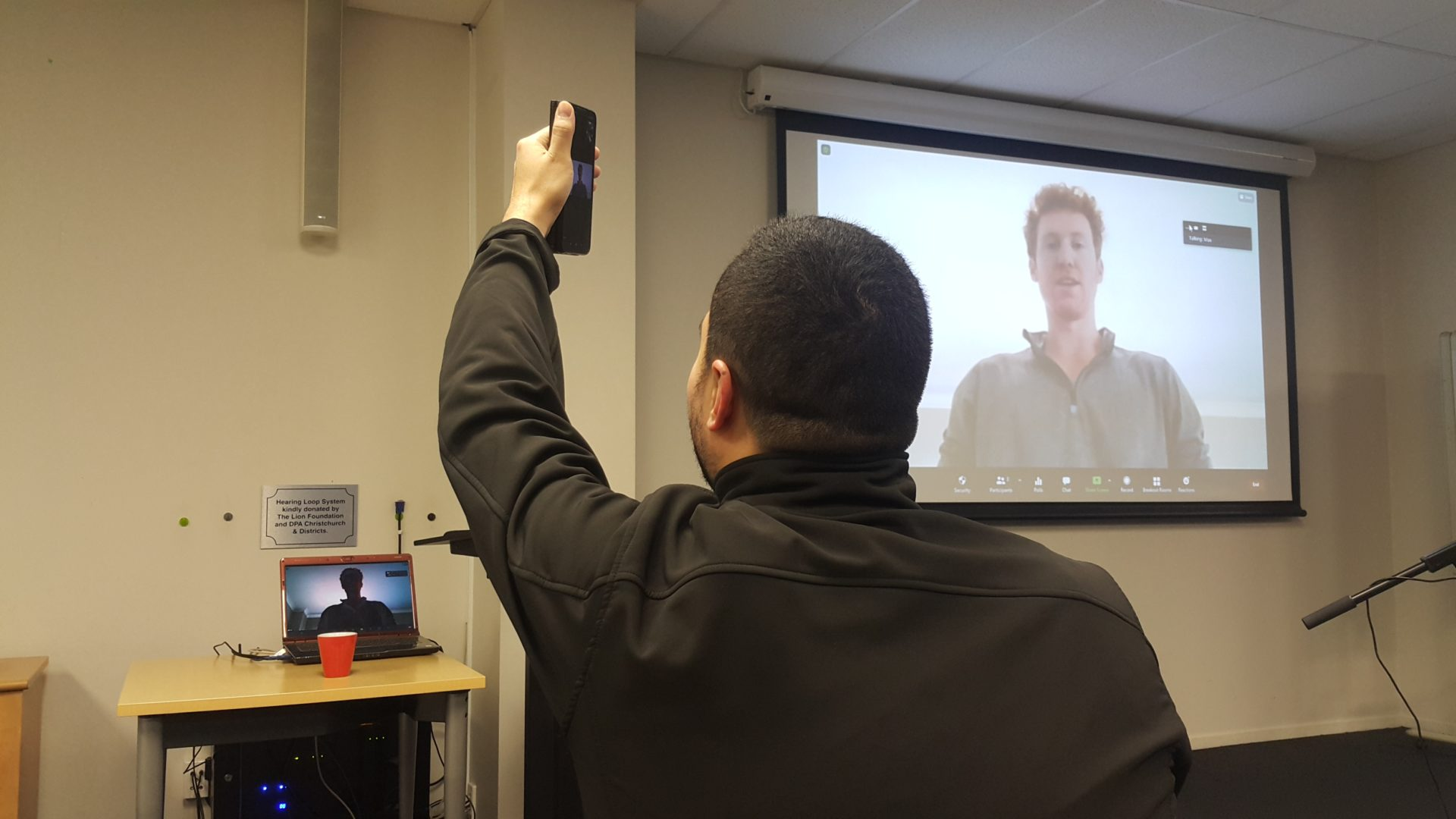 Man taking photo of person presenting on a large screen via Zoom