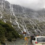 Line of cars waiting in traffic to enter Milford Sound alongside a massive rockface on the left